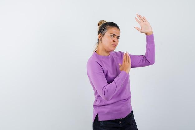 Signora in camicetta di lana che mostra il gesto del colpo di karate e sembra dispettosa