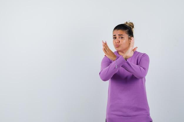 Signora in camicetta di lana che mostra gesto di rifiuto e sembra seria