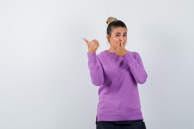 Signora in camicetta di lana che mostra gesto di silenzio con il pollice in su e sembra sicura