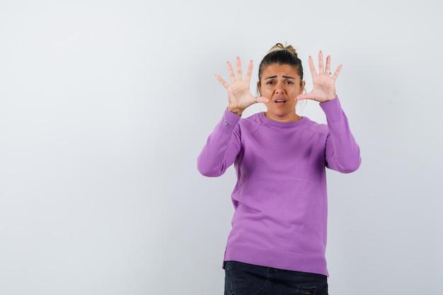 Signora in camicetta di lana che mostra il gesto di arresto e sembra spaventata