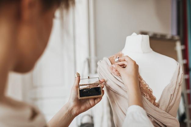 ファッションデザイナーとして働き、新しいドレスを作成する女性