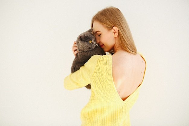 Lady in yellow dress with open back holds grey cat on her shoulder