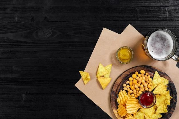 검은색 나무 테이블 너트 칩에 있는 라거 맥주와 스낵은 카피스페이스가 있는 위쪽 전망