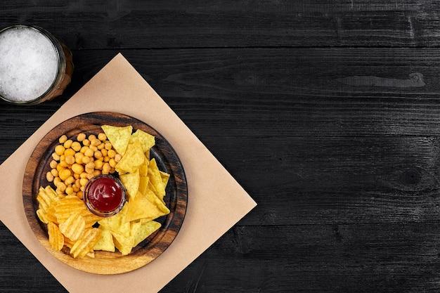コピースペースと黒い木製のテーブルナッツチップトップビューのラガービールとスナック