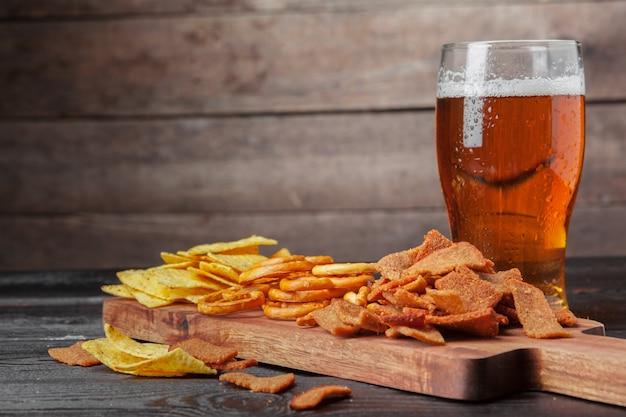 Лагер пиво и закуски на деревянный стол. орехи, чипсы, крендель