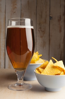 Lager beer in glass and potato chips on wooden