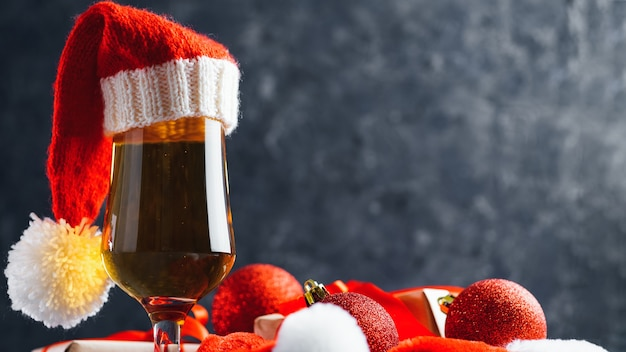 Lager beer in santa hat on dark background and gifts for new year or christmas