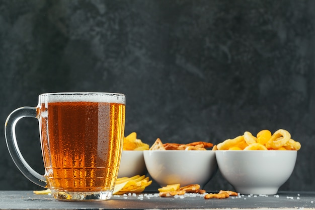 Lager beer and snacks on stone table. cracker, chips side view