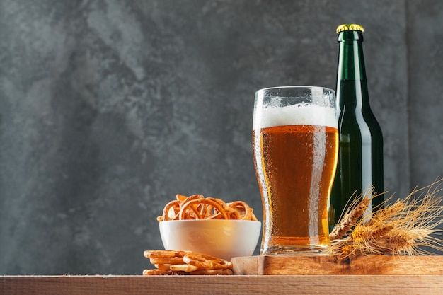 Lager beer and snacks on stone table.