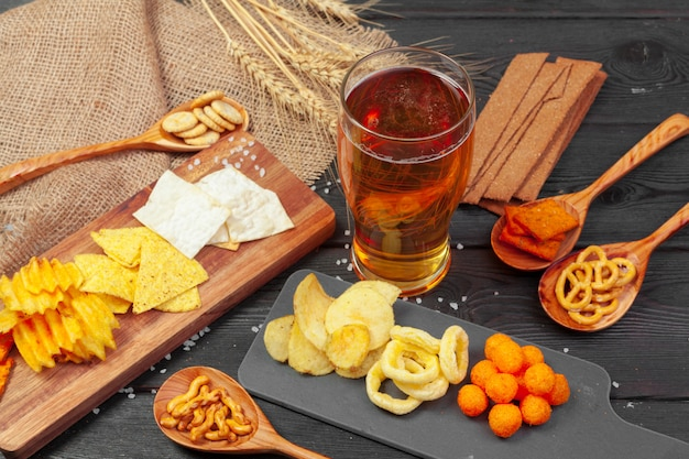 Lager beer and snacks on wooden table.