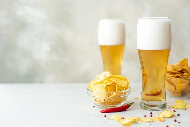 Светлое пиво с острыми картофельными чипсами в высоких стаканах на белом столе
