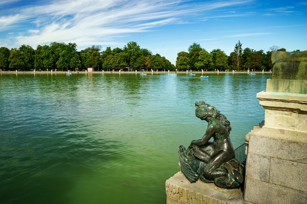 Lago del retiro in madrid with roman statues and boats sailing on the water.