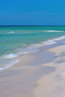 熱帯のビーチの穏やかな海のビーチの上に青い空とラグーンと白い砂浜の雲