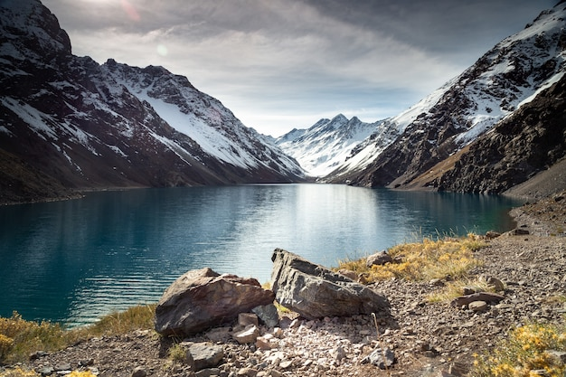 Laguna del inca lake surrounded by high mountains covered in snow in chile