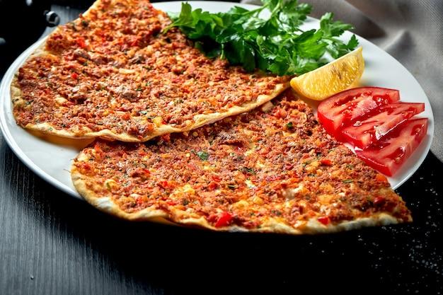 Lahmacun은 인기있는 터키 요리입니다. 블랙 테이블에 다진 양고기, 토마토, 피망을 곁들인 얇고 바삭한 또띠아