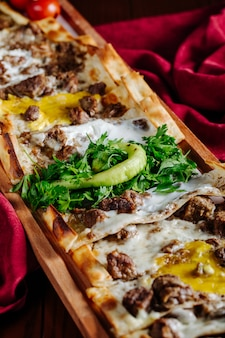 Lahmacun slices with meat and oily stuff and herbs on it on a red tablecloth.