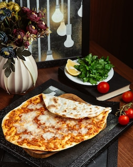 Lahmacun on wooden board with lemon and green