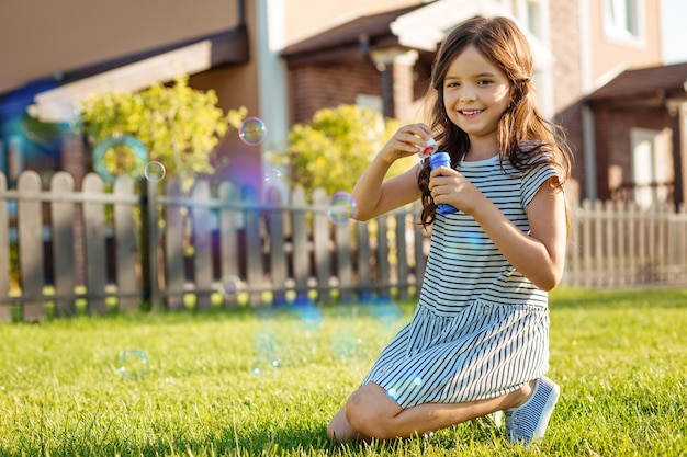 Laid-back weekend. adorable little girl sitting on the grass and playing with soap bubbles while posing for the camera