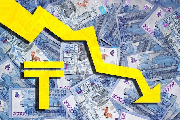 Выложенные на поверхность банкноты 20000 тенге с символом тенге и стрелкой вниз.