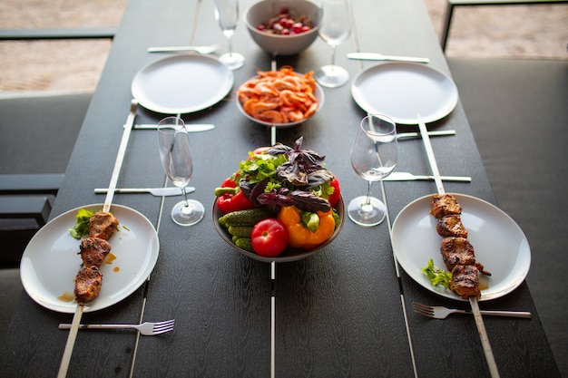 夏のテラスに4人用のテーブルを置いた友人のための夏のテラステラスのディナーテーブルセット