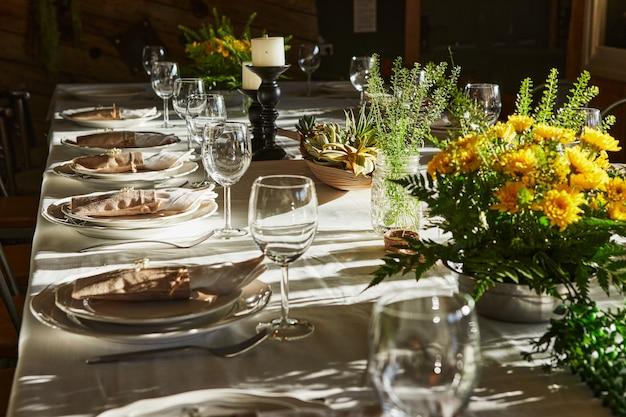 Накрытый стол со столовыми приборами и посудой в лучах заката.