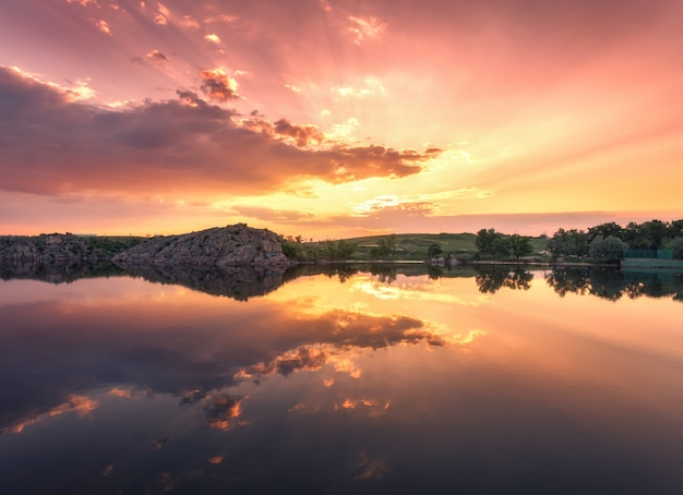 Озеро против красочного неба с облаками на закате