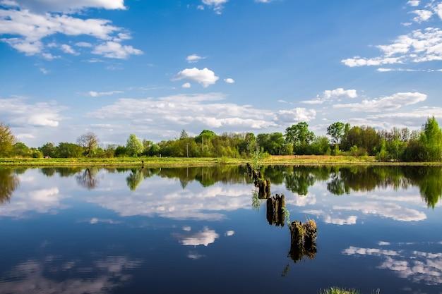 空と雲が水に映る木々の間の湖