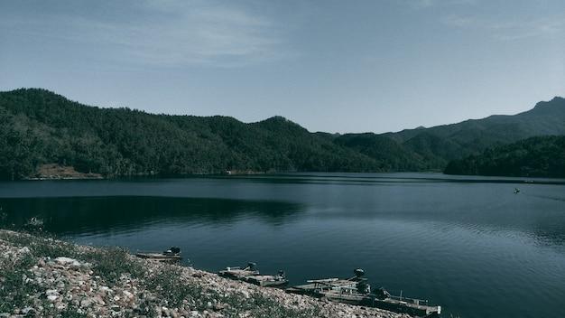 タイの湖と山の背景。ダークトーン。
