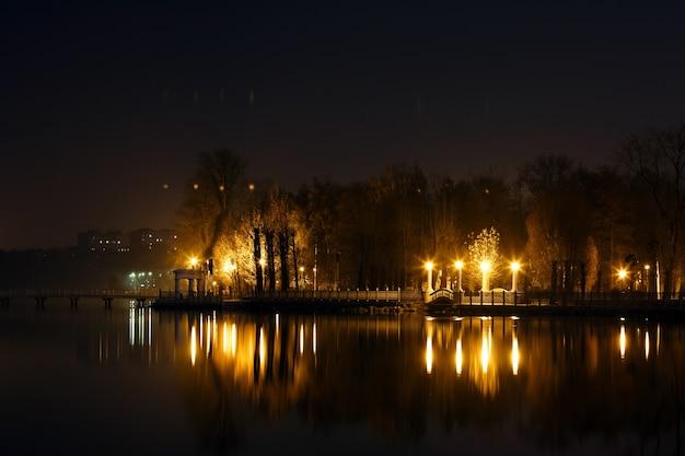 Озеро в ночное время с домом и огней