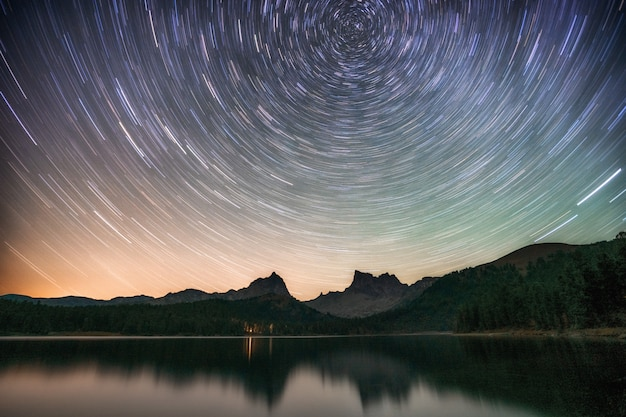 Озеро ночью с удивительным звездным небом и звездными следами с отражениями в воде.
