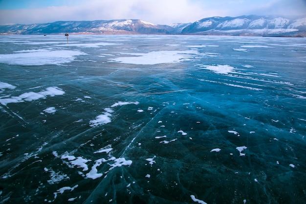 Озеро байкал зимой. прекрасный вид на замерзшую воду. текстурированные блоки чистого голубого льда. горы и пейзажи с ледяной текстурой. наблюдение за диким миром. приключение на байкале, россия