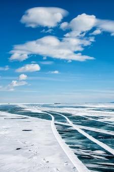 Озеро байкал зимой, поверхность озера замерзшая и достаточно прочная, чтобы проехать транспортное средство. столбы с отражающими, выстроились, чтобы определить путь для водителей.