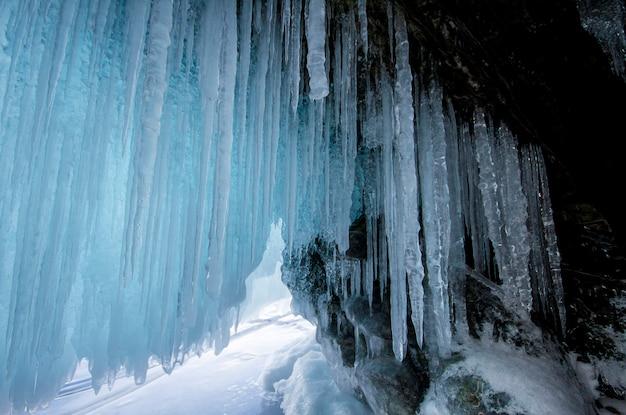 Озеро байкал - морозный зимний день. крупнейшее пресноводное озеро. озеро байкал покрыто льдом и снегом, сильным холодом и морозом, густым прозрачным голубым льдом. сосульки свисают со скал. удивительное место наследия