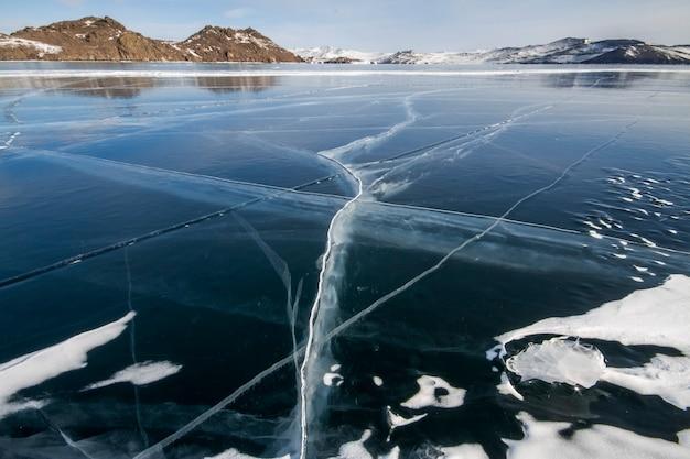 バイカル湖は凍るような冬の日です。最大の淡水湖。バイカル湖は氷と雪、強い寒さと霜、分厚い澄んだ青い氷に覆われています。岩からつららがぶら下がっています。素晴らしい場所の遺産