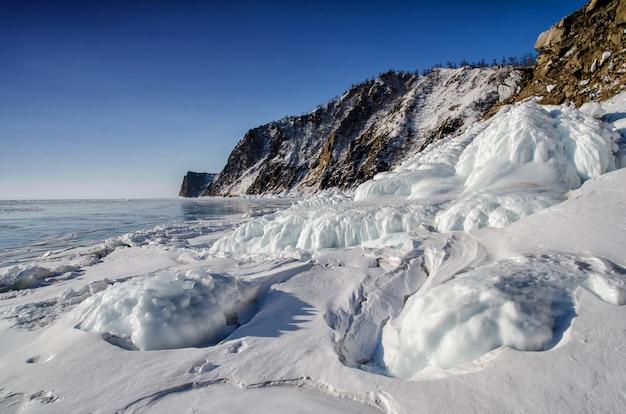 バイカル湖は氷と雪で覆われ、強く冷たく、濃く澄んだ青い氷です。つららが岩からぶら下がっています。