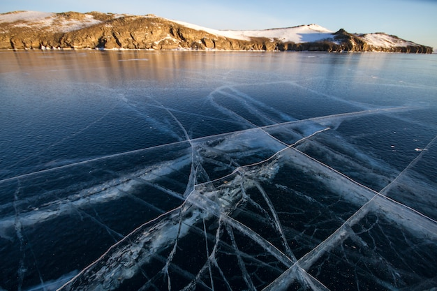 Lake baikal is covered with ice and snow, strong cold, thick clear blue ice. icicles hang from the rocks. lake baikal is a frosty winter day. amazing place, heritage, beauty of russia
