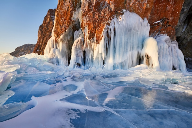 Lake baikal is covered with ice and snow, strong cold, thick clear blue ice. icicles hang from the rocks