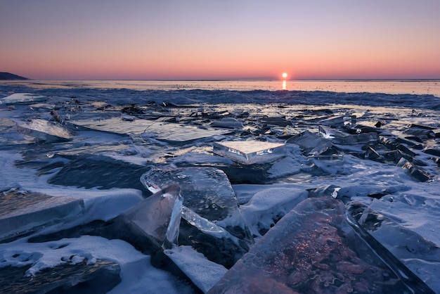 Lake baikal in siberia at sunset, a pile of beautiful ice hummocks with reflection