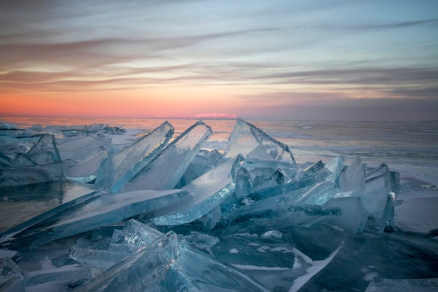 Lake baikal at sunset, everything is covered with ice and snow, thick clear blue ice. l