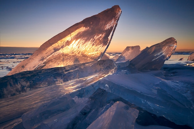 Lake baikal at sunset, everything is covered with ice and snow, thick clear blue ice