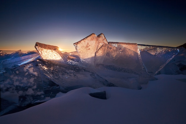 Lake baikal at sunset, everything is covered with ice and snow, thick clear blue ice.