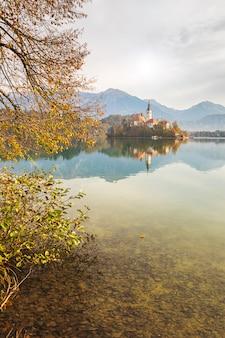 Озеро блед с красивыми отражениями в осенний сезон с красочными ветвями деревьев