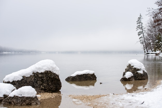 Lake bohinj with snow covered rocks looking out the water