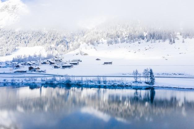 霧の日に捕獲された雪に覆われた丘のそばの湖
