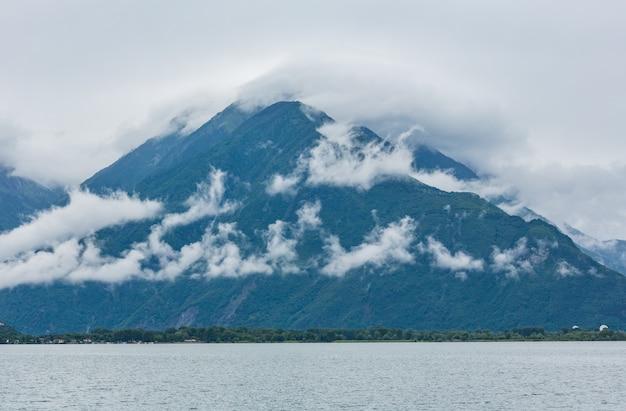 Вид лета на озеро комо (италия) с вершиной горы в облаках.