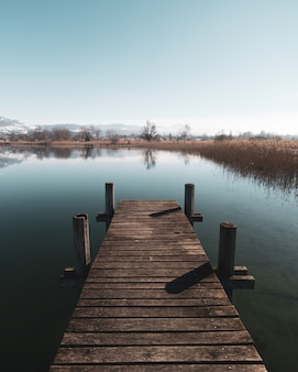 A lake dock during the off season in switzerland. calm waters and reflections