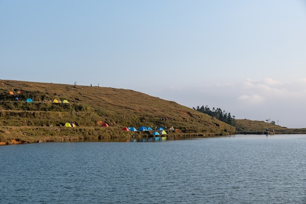 In the lake on the grassland people set up tents by the lake