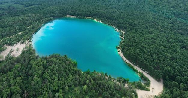 Озеро в густом сосновом лесу с высоты птичьего полета