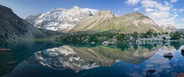 美しい反射を持つタジキスタンのファン山地の湖