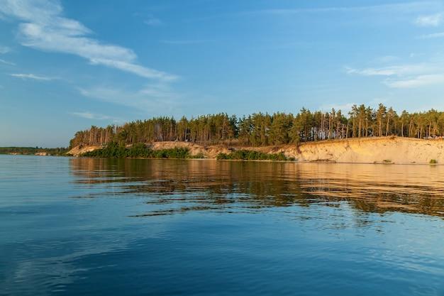 숲에서 호수입니다. 숲은 해안을 따라 자랍니다. 해안을 따라 숲입니다.